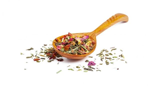 Wysuszona herbata na drewnianej łyżce, odosobnionej na bielu