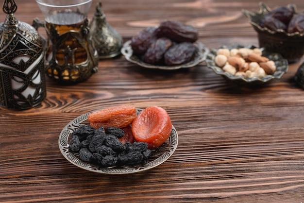 Wysuszona morela i czarna rodzynka na kruszcowym talerzu na drewnianym textured tle