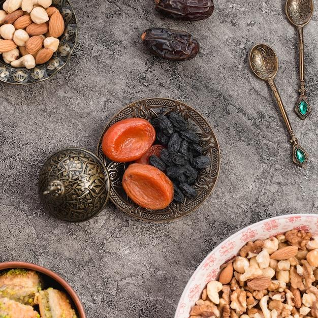 Wysuszona morela i czarna rodzynka na kruszcowym talerzu z dokrętkami na betonowym tle