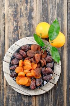 Wysuszone morele w talerzu z datami i pomarańcze odgórnym widokiem na drewnianej i tnącej desce