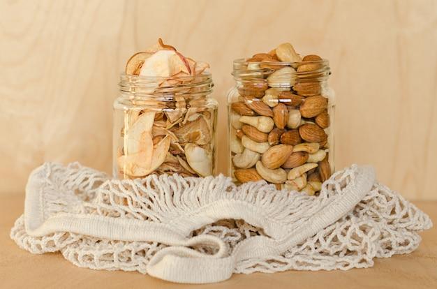 Wysuszone owoc i dokrętki w szklanym słoju w smyczkowej torbie na drewnianym tle.
