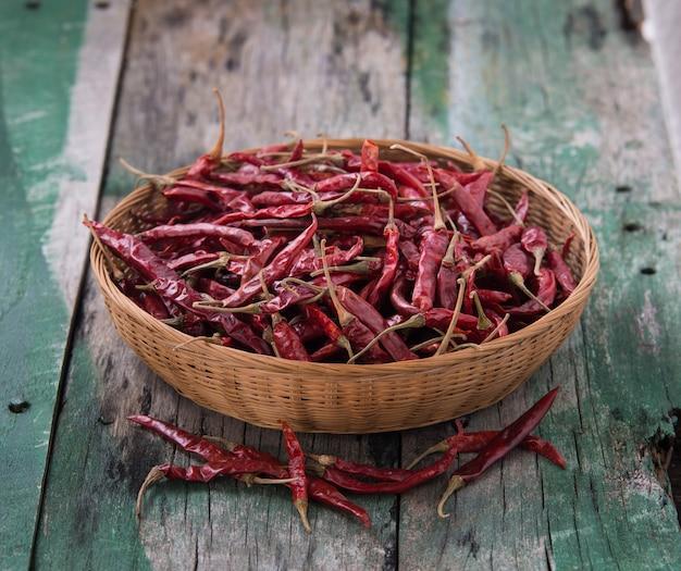 Wysuszony chili w koszu na starym drewnianym stole