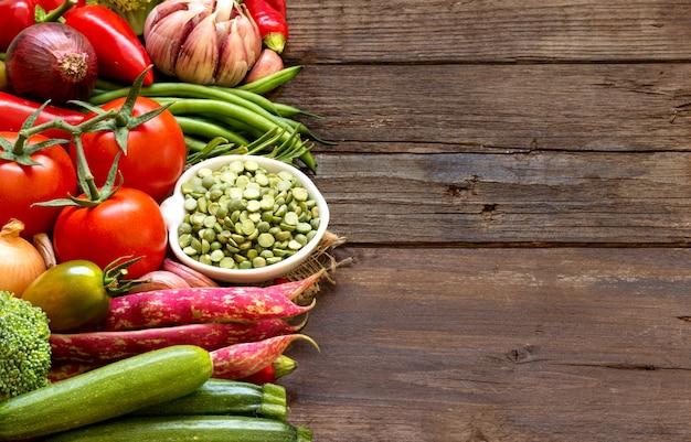 Wysuszony zielony groszek w pucharze i warzywach na drewna zakończeniu up z odbitkową przestrzenią
