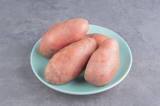 Wyświetlacz ziemniaków w talerzu na marmurowej powierzchni