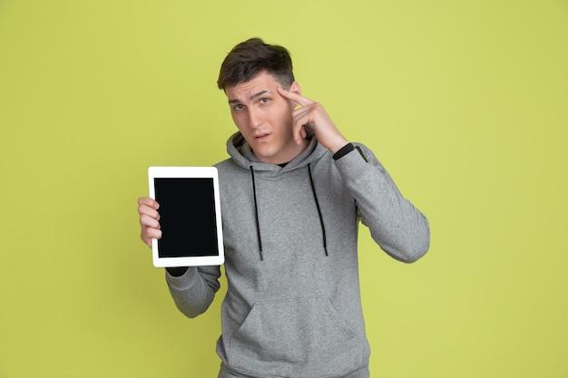 Wyświetlam pusty ekran tabletu. portret mężczyzny rasy kaukaskiej na białym tle na żółtej ścianie. zakręcony model w codziennych ubraniach.