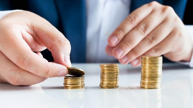 Wyświetlić zbliżenie mężczyzna biznesmen co wieże monet na białym biurku.