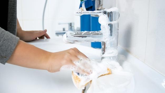 Wyświetlić zbliżenie młoda kobieta mycie umywalki w łazience z pianką detergentową i gąbką.