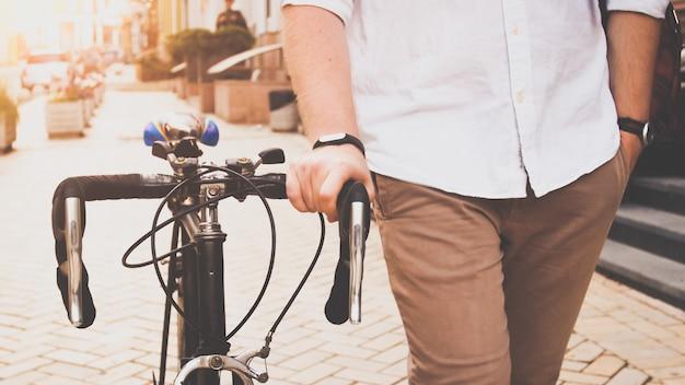 Wyświetlić zbliżenie młody człowiek spaceru z rocznika rowerów na ulicy.