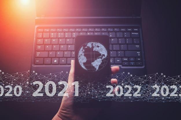 Wyświetlono wirtualny hologram globu, świat 2021 na tle laptopa smartfona i klawiatury.