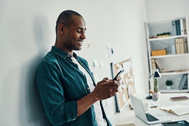 Wysyłam do kogoś sms-y. przystojny młody afrykański mężczyzna w koszuli przy użyciu smartfona stojąc w biurze