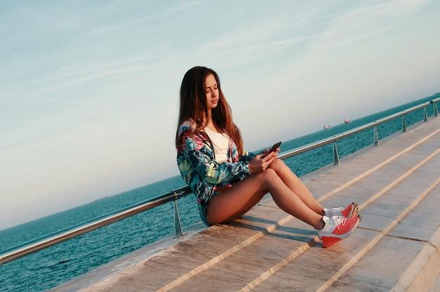 Wysyłam sms-y do przyjaciela. atrakcyjna młoda kobieta korzystająca ze smartfona w pobliżu plaży na świeżym powietrzu