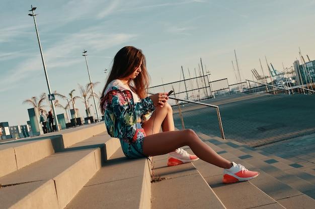 Wysyłam sms-y do przyjaciela. atrakcyjna młoda kobieta w odzieży sportowej za pomocą smartfona siedząc na schodach na zewnątrz