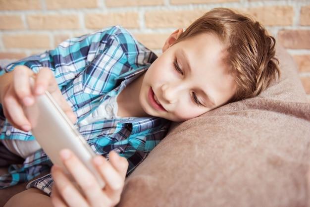 Wysyłanie wiadomości do przyjaciół przez nastolatka na telefonie komórkowym leżącym na kanapie w salonie w domu
