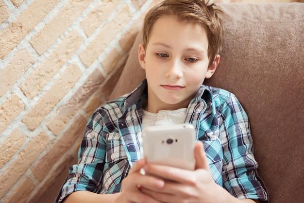 Wysyłanie wiadomości do znajomych przez nastolatka na telefonie komórkowym leżącym na kanapie w salonie w domu