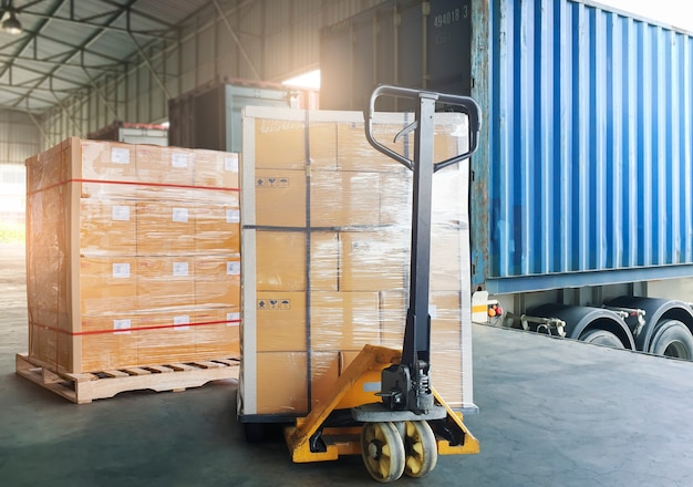 Wysyłka ładunków na paletach samochód ciężarowy ciężkie skrzynie ładunkowe z ręcznym wózkiem paletowym czekającym na załadowanie do kontenera