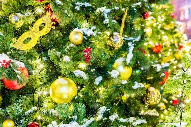 Wyszczególnia strzał choinek gałąź z bożenarodzeniowymi zabawkami, światłami, śniegiem i żółtą karnawałową maską.