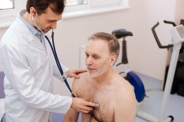 Wyszkolony wybitny młody specjalista przeprowadzający regularne badania kontrolne i używający stetoskopu podczas konsultacji z pacjentem