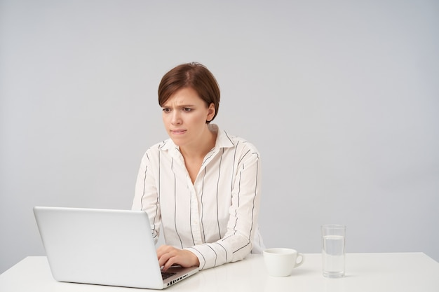 Wyszła młoda ładna brązowowłosa dama z krótką modną fryzurą, trzymając ręce na klawiaturze i patrząc z niepokojem na ekran swojego laptopa, siedząc na białym