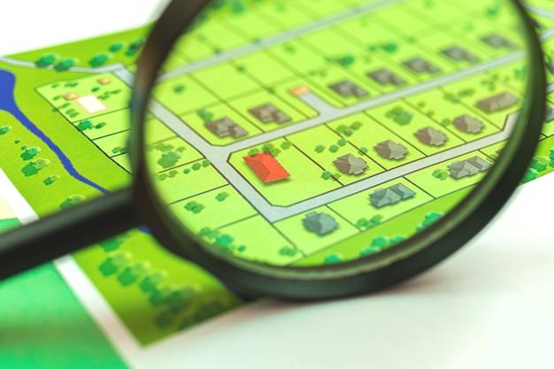 Wyszukaj nieruchomość ze szkłem powiększającym, biurko z mapą, nieruchomość z nowym zdjęciem domu