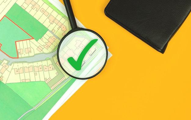 Wyszukiwanie działki budowlanej pod budowę domu, szkło powiększające na mapie katastralnej, zdjęcie w widoku z góry