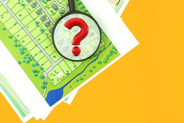 Wyszukiwanie nieruchomości z mapą, koncepcja wybierz działkę budowlaną pod budowę domu, znak zapytania z lupą, działkę na sprzedaż, widok z góry zdjęcie biurka
