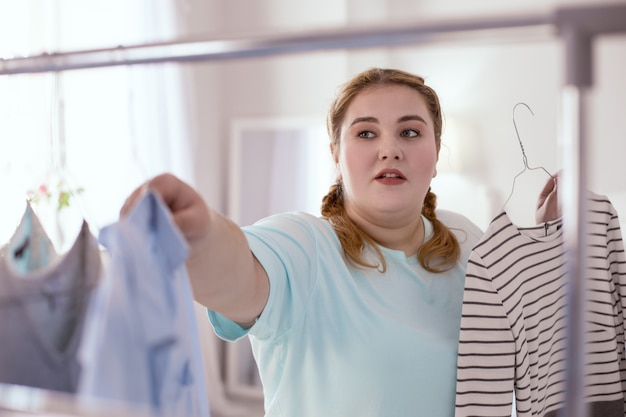 Wyszukiwanie sukni. przyjemna rudowłosa kobieta, która szuka więcej sukienek do przymierzania