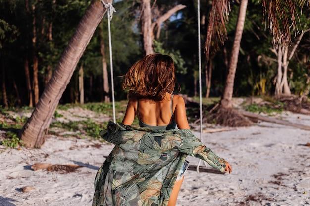 Wytatuowana kaukaska kobieta w dżinsowych szortach i zielonym modnym topie na plaży