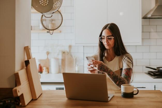 Wytatuowana kobieta korzystająca z telefonu i laptopa w domu