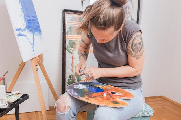 Wytatuowana kobieta miesza farby na palecie