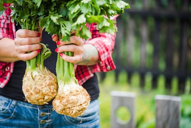Wytatuowana kobieta millennials gospodarstwa seler w ogrodzie