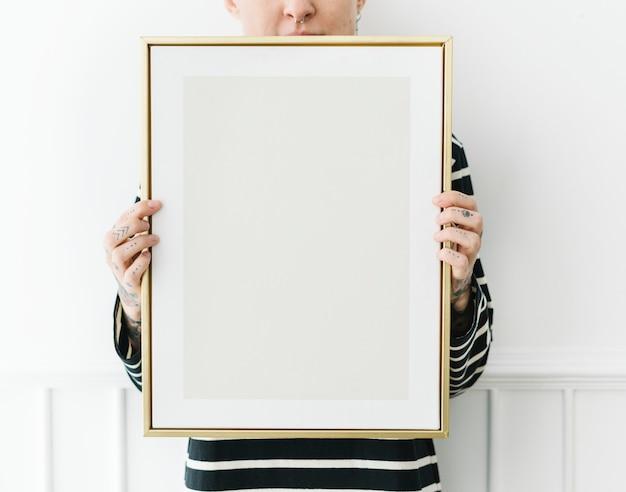 Wytatuowana kobieta trzymająca pustą ramkę na zdjęcia