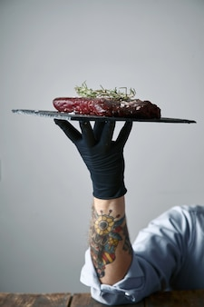 Wytatuowana ręka w czarnej rękawiczce trzyma kamienny talerz ze stekiem gotowym do przyrządzenia