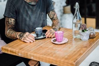 Wytatuowane ręce. ręce trzymając szklankę z kawą.