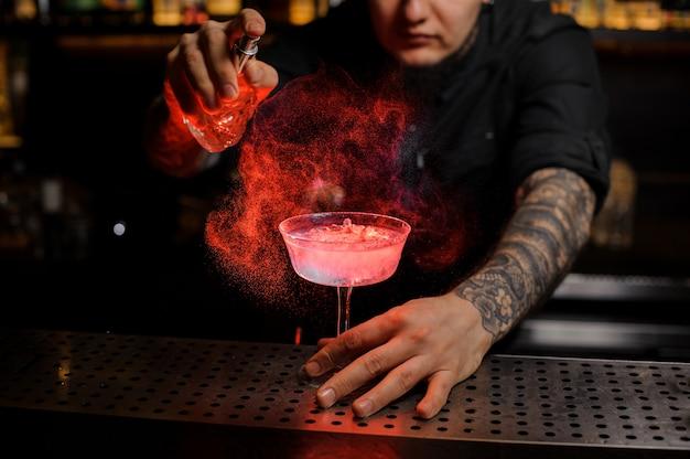 Wytatuowany barman rozpylający pyszny koktajl ze specjalnego waporyzatora na blacie barowym