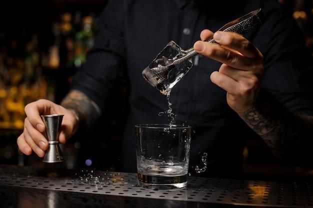 Wytatuowany barman wkłada kostkę lodu do kieliszka koktajlowego