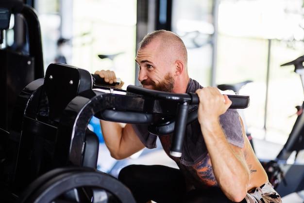 Wytatuowany brodaty mężczyzna robi przysiady na maszynie treningowej
