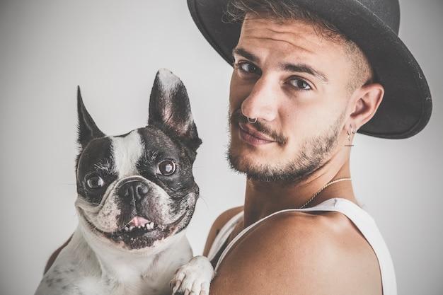Wytatuowany chłopiec z kolczykami z psem buldog francuski w ramionach na białym tle