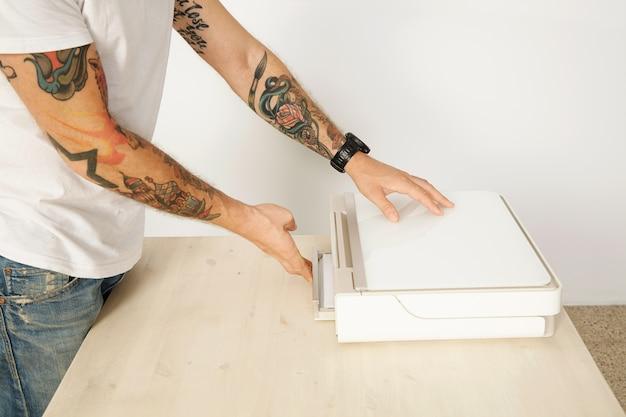 Wytatuowany człowiek nierozpoznawalny zamyka tacę papieru urządzenia wielofunkcyjnego skaner drukarki domowej, na białym tle