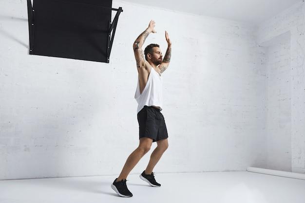 Wytatuowany i umięśniony atleta robi pajacyki na białym tle na białym murem obok czarnego drążka, patrząc po prawej stronie
