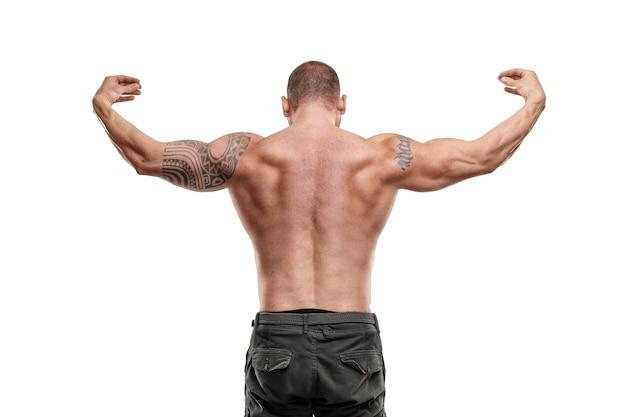 Wytatuowany kulturysta mężczyzna pozowanie na białej ścianie. trening fitness