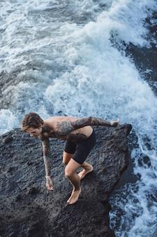 Wytatuowany mężczyzna leży na skraju urwiska. rozpryski fal oceanu.