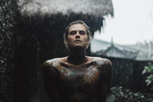 Wytatuowany mężczyzna pozowanie w deszczu