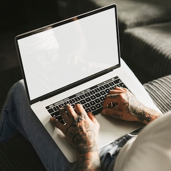 Wytatuowany mężczyzna pracujący na ekranie laptopa