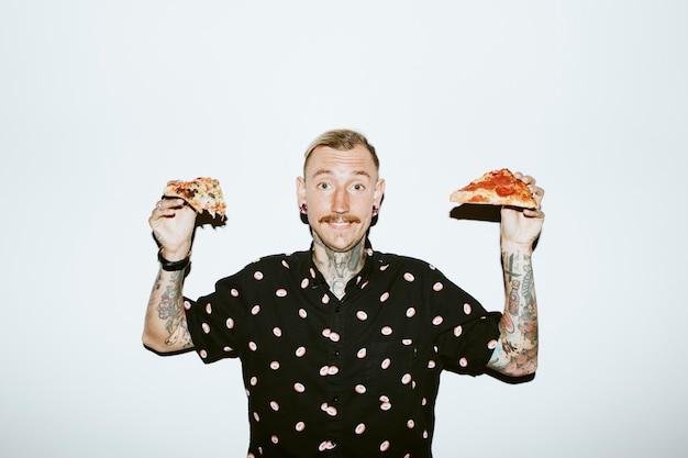 Wytatuowany mężczyzna trzymający pizzę w dłoniach
