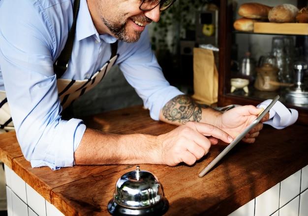 Wytatuowany mężczyzna używa cyfrową pastylkę w piekarni sklepie