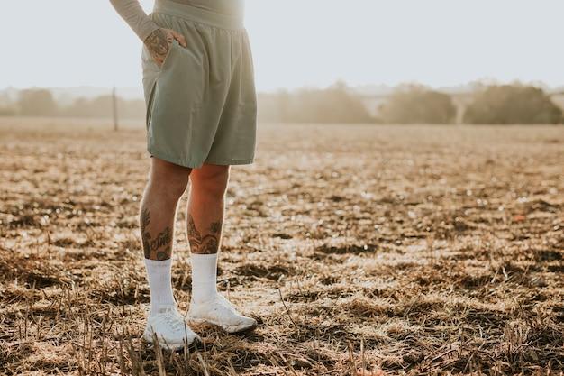 Wytatuowany mężczyzna w spodenkach do biegania stojący na wsi o zachodzie słońca