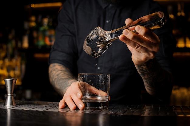 Wytatuowany miksolog wkłada kostkę lodu do kieliszka koktajlowego