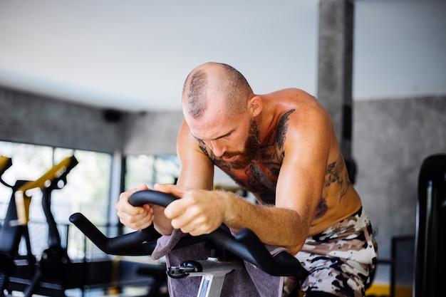 Wytatuowany, muskularny, brodaty mężczyzna ćwiczy cardio na rowerze w siłowni w pobliżu dużego okna z widokiem na drzewa na zewnątrz