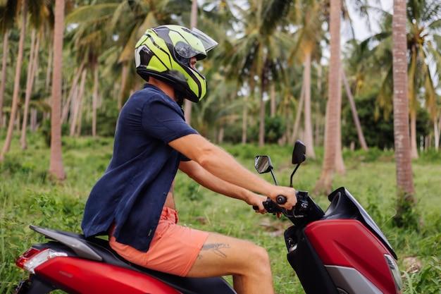 Wytatuowany siłacz na polu tropikalnej dżungli z czerwonym motocyklem