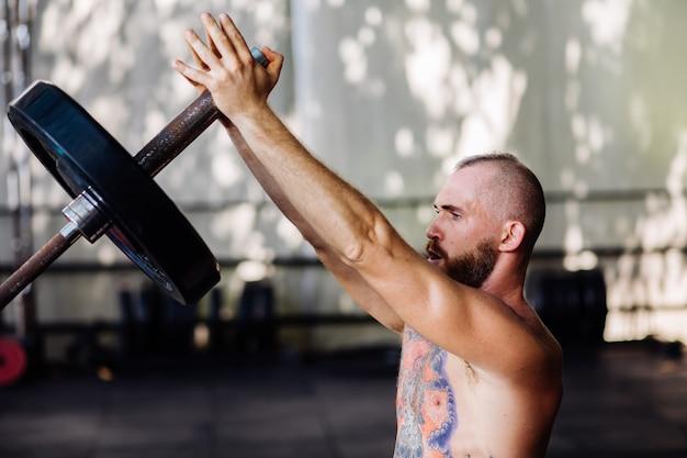 Wytatuowany siłacz z brodą na siłowni